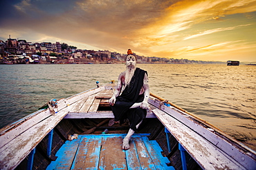 Indian Hindu Sadhu (saint) in boat on River Ganges in Varanasi, Uttar Pradesh, India, Asia