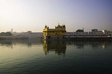 The Golden Temple at sunrise through fog, Amritsar, Punjab, India, Asia