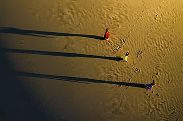 People are walking across Nam Cuong sand dunes, Ninh Thuan, Viet Nam to return home.