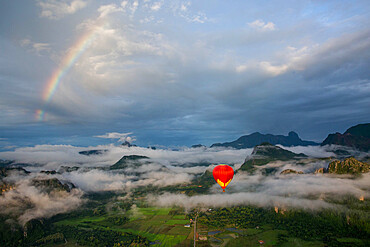 A sunrise over Vang Vieng, with a rainbow over the clouds, as a hot air balloon rises in the foreground, Laos, Indochina, Southeast Asia, Asia