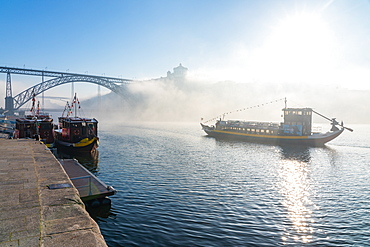 Boat sailing down the River Douro in early morning mist with Dom Luis I Bridge in background, Porto, Portugal, Europe