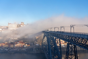 Dom Luis I Bridge with tram and view of Porto in the early morning mist, Porto, Portugal, Europe