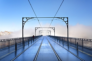 Tram tracks in the early morning mist running over Dom Luis I Bridge in Porto, Portugal, Europe