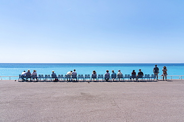 Line of people on chairs looking out to the sea, Nice, Alpes Maritimes, Cote d'Azur, French Riviera, Provence, France, Mediterranean, Europe