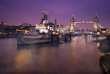 HMS Belfast with Tower Bridge in background, shot early morning with Thames Mist and city lights, London, England, United Kingdom, Europe - 1328-3