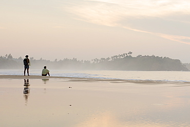 Two men watching the sunrise on Talalla beach, Sri Lanka, Asia