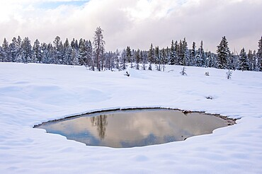 Snowscape of reflection of sky in thermal feature, Yellowstone National Park, Wyoming, United States
