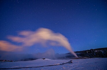 Old Faithful geyser under a starry sky, Yellowstone National Park, Wyoming, United States