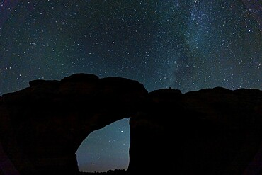 Starry sky viewed through Broken Arch, Arches National Park, Utah, United States of America, North America