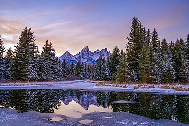 Evening light and reflection of Teton Range in snowy pond, Grand Teton National Park, Wyoming, United States of America, North America
