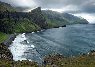 View over a hidden bay with the sun filtering through the clouds, Faroe Islands, Denmark, Europe