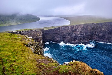 Cliffs of Traelanipa with the lake above the ocean, Faroe Islands, Denmark, Europe