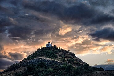 Cloudy sunset on a small church on the top of a hill, Thessaly, Greece, Europe