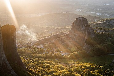 Sunset light and sun beams in the smoke in Meteora, Thessaly, Greece