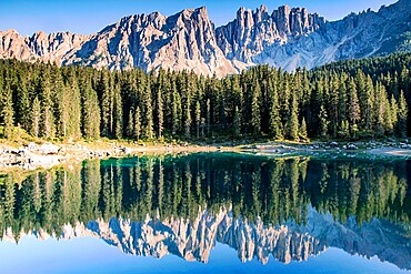 Latermar and larch forest reflected in the Carezza Lake at sunset, Carezza, Trentino-Alto Adige, Italy, Europe