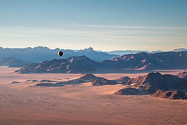 Rocky mountains, aerial view with hot air balloon flying over it, Namibia, Africa