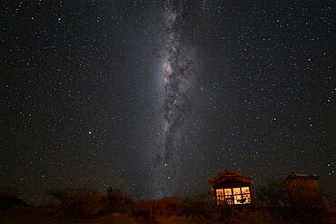 South hemisphere Milky Way and a small illuminated hut, Namibia, Africa