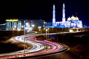 Long exposure cityscape night shot with a blue mosque and a street with car trails, Muscat, Oman, Middle East