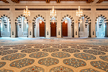 Male praying room of the Sultan Qaboos Mosque with decorated carpet and many arches, Muscat, Oman, Middle East
