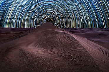 Concentric circumpolar star trail above sand dunes in the Rub al Khali desert, Oman, Middle East