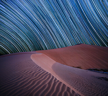 Equatorial star trail above sand dunes in the Rub al Khali desert, Oman, Middle East