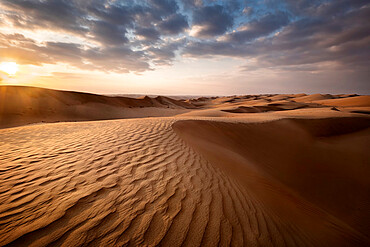 Sand dunes at sunset in the Wahiba Sands desert with clouds in the sky, Oman