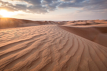 Sand dunes at sunset in the Wahiba Sands desert with clouds in the sky, Oman, Middle East