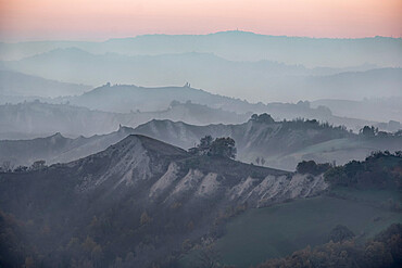 Dusk over hills where many layers are covered by fog, Emilia Romagna,Italy