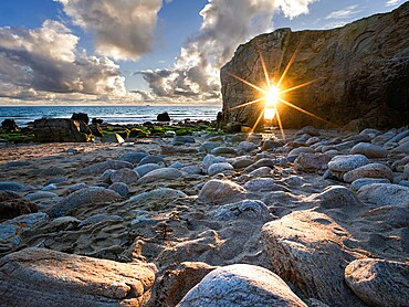 Sun burst aligned with the natural arch of Port Blanc, Quiberon, Brittany, France, Europe