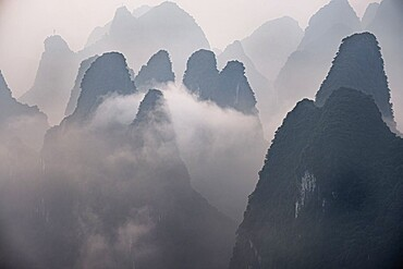 Misty morning with fog and low clouds on the peaks above Li River, Guangxi, China, Asia