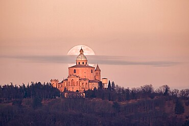 Full moon and a small cloud behind San Luca church (Madonna di San Luca). Bologna, Italy, Europe