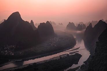 Pink sunrise on the Li River and the famous Yangshuo mountains, Yangshuo, Guangxi, China, Asia