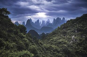 Yangshuo mountains with dark clouds framed by hills, Yangshuo, Guangxi, China, Asia