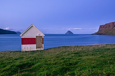 Blue hour at a small wooden house by the sea on Suduroy, Faroe Islands, Denmark, Europe