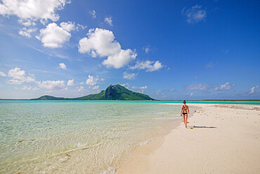 An athletic woman in a bikini walks along the white sandy shoreline of the turquoise lagoons in Tahiti