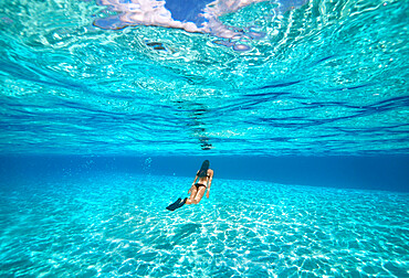 A young woman swimming underwater in clear blue shallow lagoon with a sandy bottom, French Polynesia, South Pacific islands, Pacific