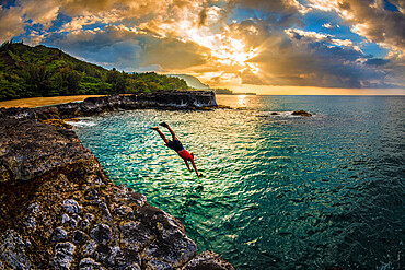 A young man dives into the calm sea on the northern rocky coastline of Kauai at sunset, Hawaii, United States of America, Pacific