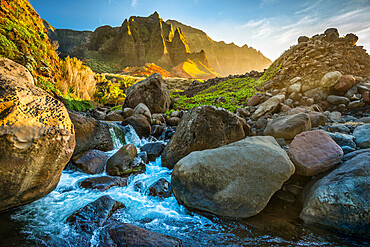 A mountain stream flows down at sunset in Kauai's Kalalau Valley, Hawaii, United States of America, Pacific
