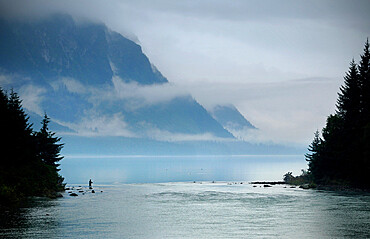 A fisherman on the misty banks of Chilkoot Lake in Haines, Alaska at sunset.