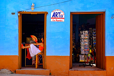 A woman with a fan relaxes in a doorway, Trinidad, Sancti Spiritus, Cuba, West Indies, Central America