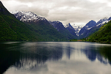 Snow-capped mountains reflected in the still waters of a Norwegian fjord, Stryn, Vestland, Norway, Scandinavia, Europe