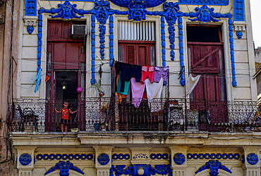 Small child in doorway on a balcony with drying clothes, Havana, Cuba, West Indies, Central America