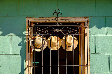 Three straw hats hang on an iron grate in a window, Trinidad, Cuba, West Indies, Central America