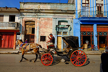 A horse-drawn carriage driver waves as he passes by, Cardenas, Matanzas, Cuba, West Indies, Central America