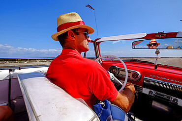 Man in straw hat drives vintage car along the Malecon, Havana, Cuba, West Indies, Central America