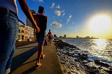 People walk along the Malecon as the sun sets, Havana, Cuba