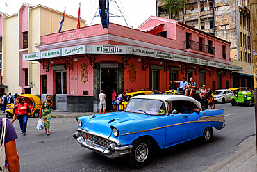 Pedestrians, antique cars, and a horse-drawn carriage travel the streets of Havana, Havana, Cuba