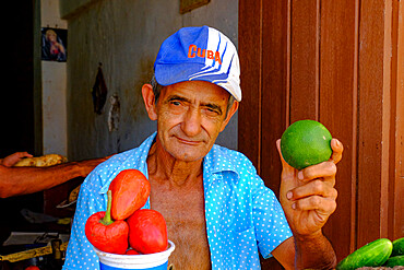 A man at a vegetable stand holds up a lime, Trinidad, Cuba, West Indies, Central America
