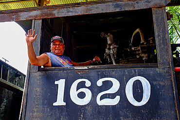 A smiling man waves from the engine of a train, Cienfuegos, Cuba, West Indies, Central America