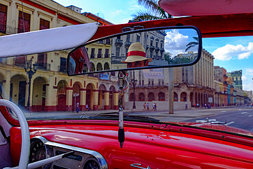 Taxi driver in straw hat seen in rear-view mirror of vintage car, Havana, Cuba, West Indies, Central America